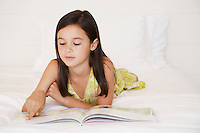 Girl reading story book lying on bed