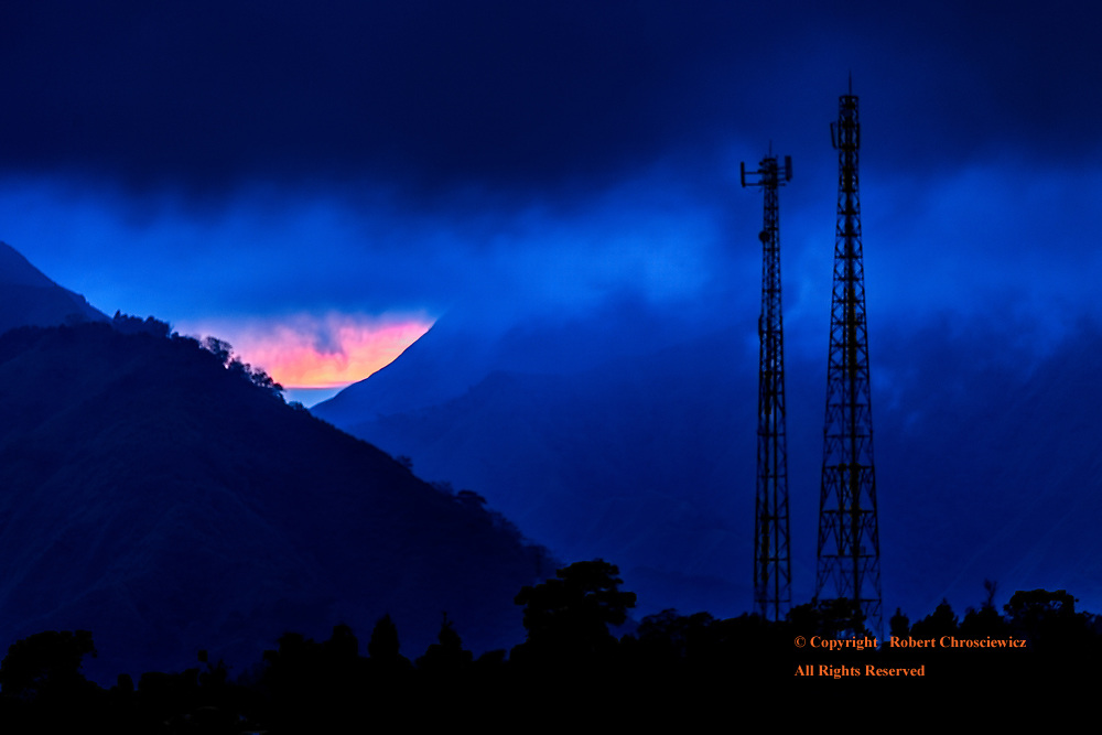 Blue Sunrise: Morning finds a mountainous valley shrouded in layers blue, as heavy cloud cover and mist engulf two telecommunication towers that rise before a distant sunrise over Mentagi, Lombok Indonesia.