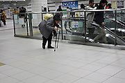 senior woman walking with the help of two walking sticks in train station Yokohama Japan