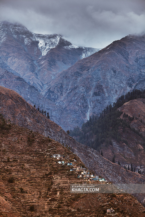 A village on top of a mountain cliff in Bharmour, Chamba, Himachal Pradesh, India
