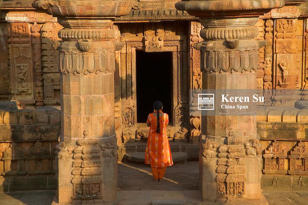 Indian woman praying at Mukteswar Mandir with with ornate carving, Bhubaneswar, Orissa, India