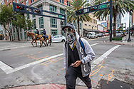 Luis Gato, 42, wears a protective mask against the COVID19 pandemic as a City of Miami Mounted Patrol Officers ride their horses along Flagler Street in downtown Miami on Wednesday, April 1, 2020.