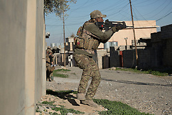 Licensed to London News Pictures. 20/02/2017. Albu Saif, Iraq. An Iraqi Emergency Response Division soldier fires at an ISIS fighter in the village of Albu Saif during the offensive to retake western Mosul from Islamic State militants.<br /> <br /> The settlement of Albu Saif is located on high ground overlooking Mosul Airport and as such is a strategic point that needs to be taken as part of the operation to retake the western side of Mosul. Photo credit: Matt Cetti-Roberts/LNP