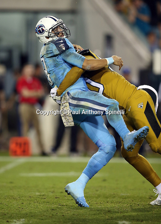 Tennessee Titans quarterback Marcus Mariota (8) gets tackled by Jacksonville Jaguars defensive end Andre Branch (90) after throwing a pass with about two minutes left in the fourth quarter during the 2015 week 11 regular season NFL football game against the Jacksonville Jaguars on Thursday, Nov. 19, 2015 in Jacksonville, Fla. The Jaguars won the game 19-13. (©Paul Anthony Spinelli)