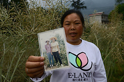 59601375  .The 43-year-old Yue Fenglian poses for photo with an old picture in the quake-hit Longmen Village, southwest China's Sichuan Province, May 4, 2013. The old picture of Yue with a relative was taken in 1990. Old photos are not daily necessities for who just suffered a 7-magnitude earthquake, but they are still cherished as they recorded peoples past life and recalled memories, May 4, 2013.  Photo by: i-Images.UK ONLY