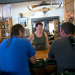 Owner Kathy Stone (center) laughs with lunch customers at the Fall Creek Lodge and Marina in the Fall Creek area or Elmore County, Idaho. The business survived the Elk Complex fire which came through the area on August 10th. Stone has only owned the restaurant for a year and said it is hard to put a number to the monetary impact of the fire. Stone said business losses caused by the fire might be alleviated by an increase in customers who are in the area for post-fire logging. Wednesday August 28, 2013