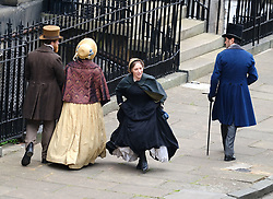"Moray Place in Edinburgh's Georgian old town was turned into 19th century London for Julian Fellowes' new ITV show ""Belgravia"".<br /> <br /> Pictured: An actress dressed as a maid checks her boots are laced up correctly but has to make some adjustments before she runs along the street.<br /> <br /> Alex Todd 
