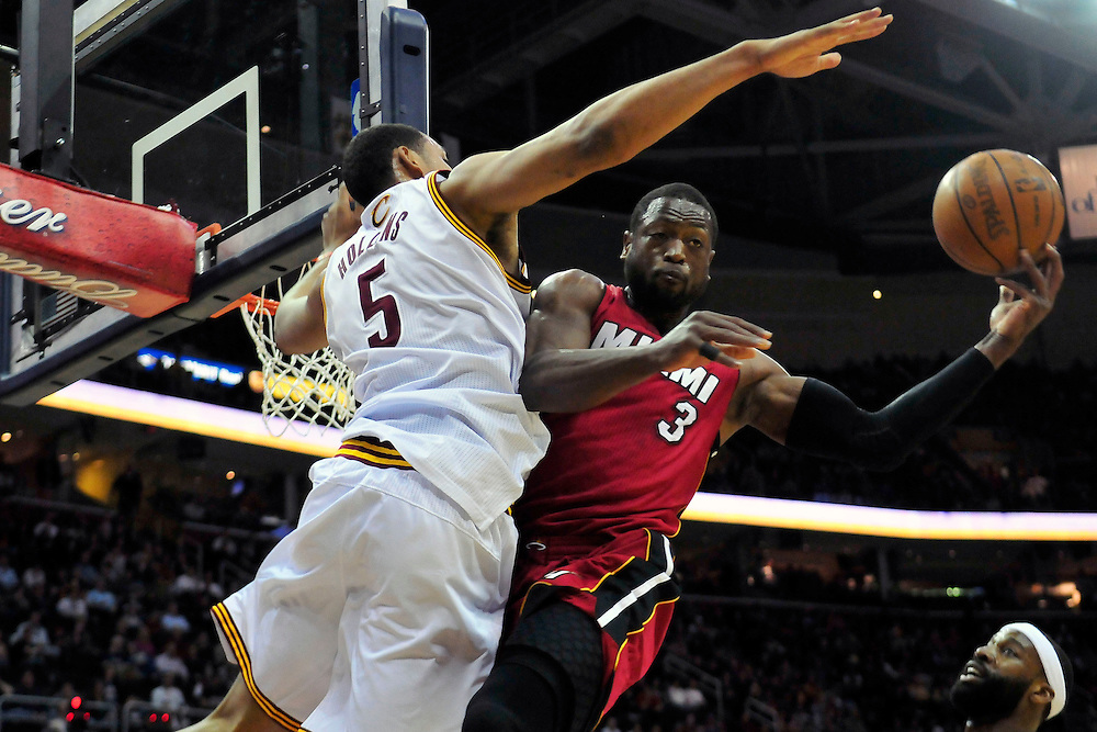March 29, 2010; Cleveland, OH, USA; Miami Heat shooting guard Dwyane Wade (3) tries to make a shot over Cleveland Cavaliers center Ryan Hollins (5) during the first quarter at Quicken Loans Arena. Mandatory Credit: Jason Miller-US PRESSWIRE