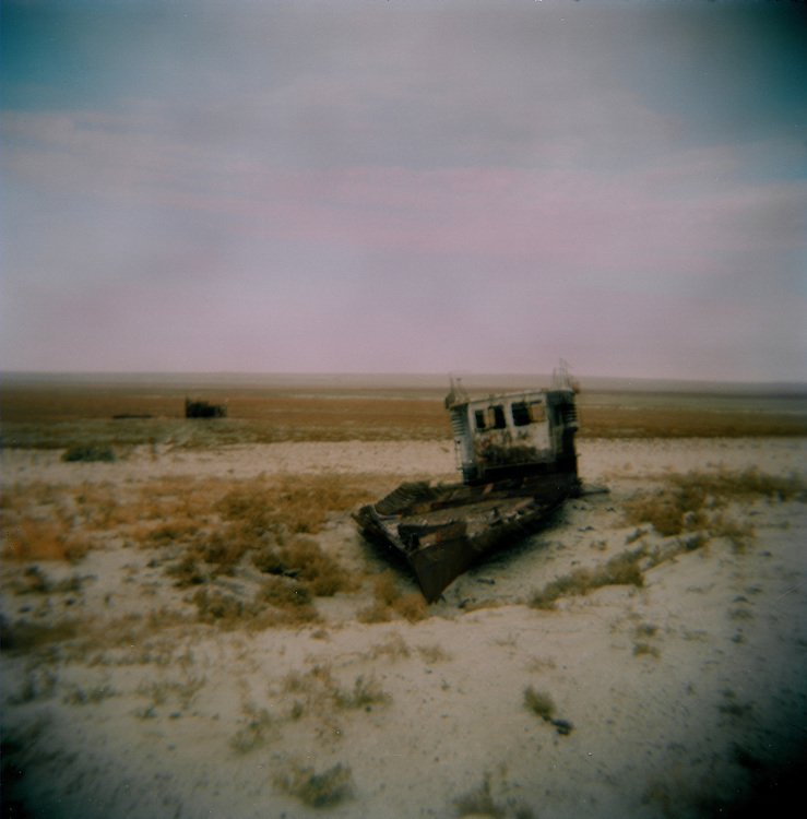 CREDIT: DOMINIC BRACCO II..SLUG:PRJ/KAZAKHSTAN..DATE:10/31/2009..CAPTION:Rusted boats at the old Aral Sea bed on Oct. 30, 2009. The small vegetation had been completely grazed over and cut down by locals by their herds or for use of firewood. The destruction of vegetation on the former sea bed allows sands to blow away and further spread the effects of desertification...Aral Sea Overview: ..During the 1960s the USSR began irrigating the waters of the Aral Sea in southern Kazakhstan to combat their growing food crisis. The Soviets severely miscalculated and water began receding quickly from the port cities. The waters continued to recede. By 2000 the water was 80 km away from the city of Aralsk, a main seaport in Kazakhstan. In 2005 with help from the World Bank, construction began on a 13km dike that locals hoped would bring the waters back to their original shores. The project raised water quality and fishing was able to resume, however four years after completion of the dike the water is still 50km from Aralsk's port. Locals seem mixed on the possibility of the sea returning after more than 40 years without the sea. Fishermen from Aralsk make a three-hour path through soft desert road along the former seabed. The only source of income for many is cattle, horses, and camels, which have, began to overgraze the areas of the former seabed and surrounding desert. Because of this nutrient rich topsoil is lifted by the wind and the process of desertification continues.  .