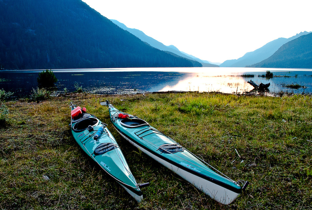 Kayaks rest on the shore of Buttle Lake at dusk, Vancouver Island BC
