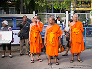 19 OCTOBER 2014 - BANG BUA THONG, NONTHABURI, THAILAND: Buddhist monks leave Apiwan Wiriyachai's cremation at Wat Bang Phai in Bang Bua Thong, a Bangkok suburb, Sunday. Apiwan was a prominent Red Shirt leader. He was member of the Pheu Thai Party of former Prime Minister Yingluck Shinawatra, and a member of the Thai parliament and served as Yingluck's Deputy Prime Minister. The military government that deposed the elected government in May, 2014, charged Apiwan with Lese Majeste for allegedly insulting the Thai Monarchy. Rather than face the charges, Apiwan fled Thailand to the Philippines. He died of a lung infection in the Philippines on Oct. 6. The military government gave his family permission to bring him back to Thailand for the funeral. His cremation was the largest Red Shirt gathering since the coup.     PHOTO BY JACK KURTZ
