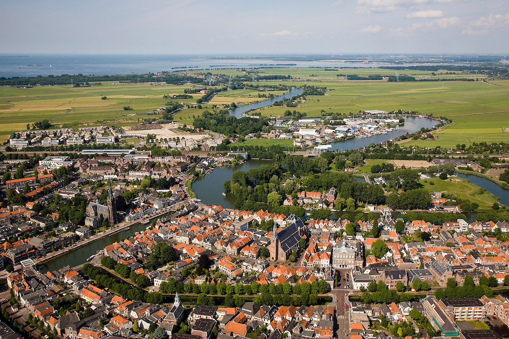 Nederland, Noord-Holland, Weesp, 17-06-2008; historische binnenstad van Weesp, oorspronkelijk vestingstad met stadswallen en bastions, deels nog herkenbaar in het stratenplan (en op de foto); deel van de verdegingswerken vormde een fort, dit torenfort de Ossenmarkt ligt op het eiland rechts van het midden, boven de kerk en in het verlengde van het Grote Plein; naar de horizon met Muiden en het IJsselmeer meandert het riviertje de Vecht; meander, stadscentrum, centrum, grachten..luchtfoto (toeslag); aerial photo (additional fee required); .foto Siebe Swart / photo Siebe Swart