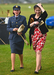 © Licensed to London News Pictures. 14/09/2012. Goodwood, UK Two women hold onto their hats in the wind. People enjoy the atmosphere at the 2012 Goodwood Revival Meeting today 14 September 2012. Participants are encouraged to dress in period dress.. Photo credit : Stephen Simpson/LNP