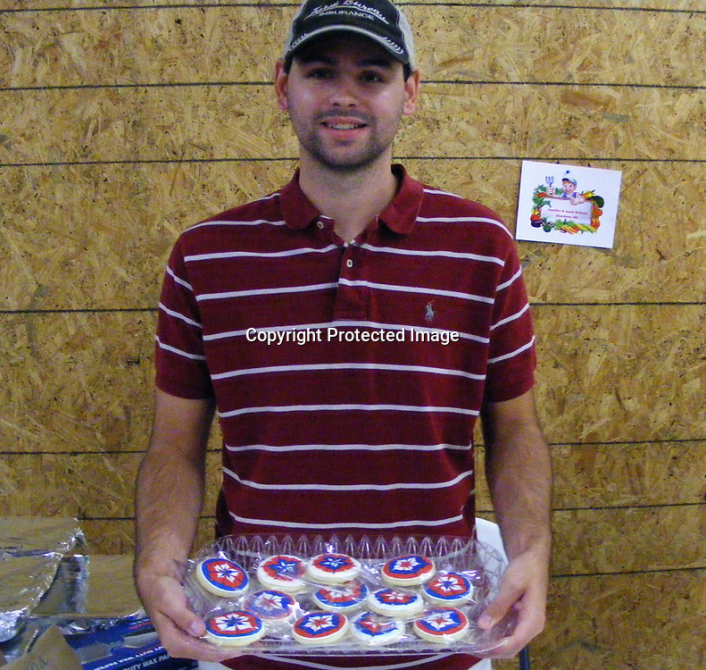 Jacob Dickens holds a plate of sugar cookies decorated with Royal frosting for the Fourth of July holiday in red, white and blue colors.