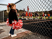 Delanie Pettit, 3, angry her mom will not allow her to go onto the field with the Heath high School cheerleading squad, watches from the sidelines as the girls warm up before the game.