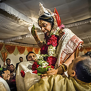 The Bengali bride, usually seated on a low wooden stool called pidi, is lifted by her brothers and taken round the groom in seven complete circles. The significance is they are winded up securely to each other. The bride removes the betel leaves for the 'shubh dhristi', or the auspicious 'viewing' of each other. The couple will now exchange garlands and the groom will proceed to the 'mandap' (marriage platform) followed by the bride.