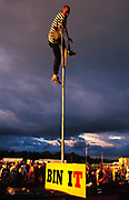 A man at top of pole on cloudy day at festival, U.K, 2000s.