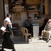 Five individuals form a traditional street scene in the Old City of Aleppo, Syria
