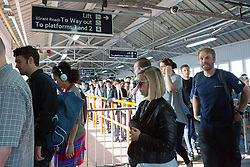 © Licensed to London News Pictures. 09/07/2015. London, UK. A one way system is put into place to managed crowded platforms at Clapham Junction station in south London. A tube strike today has closed the TfL London Underground network and has been called by Trade Unions in protest over the new all-night tube trains, due to start in mid-September.. Photo credit : Vickie Flores/LNP