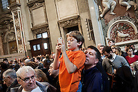 VATICAN CITY - 12 MARCH 2013: A father holds his child in his arms to help him take a picture of the 115 cardinals entering Saint Peter's Basilica for the Pro Eligendo Pontifice Mass, or the Mass for the Election of the Roman Pontiff, in Vatican City, on March 12, 2013...After the mass, cardinals are set to enter the conclave to elect a successor to Pope Benedict XVI after he became the first pope in 600 years to resign from the role. The conclave will take place inside the Sistine Chapel and will be attended by 115 cardinals as they vote to select the 266th Pope of the Catholic Church.