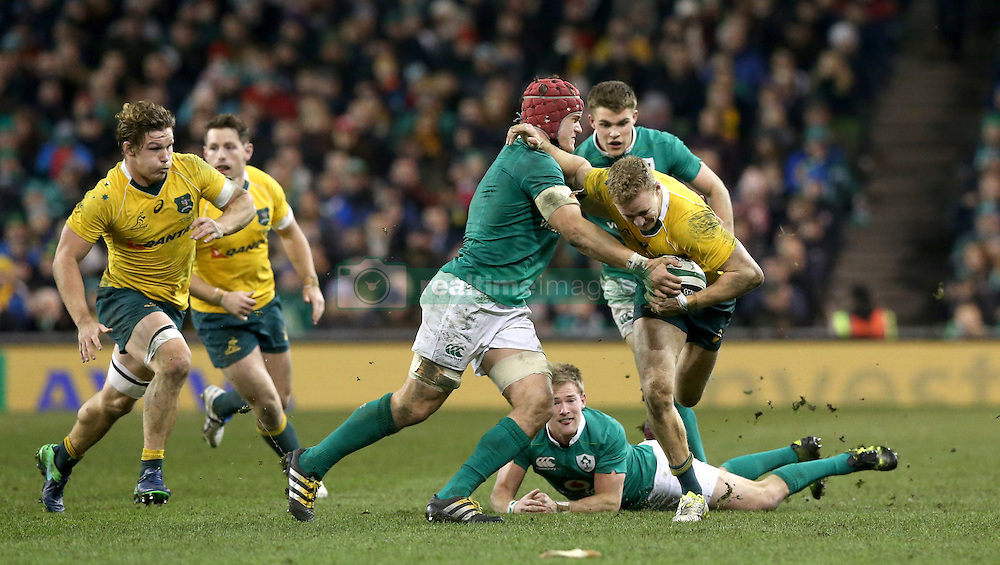Australia's Reece Hodge is tackled by Ireland's Josh Van der Flier during the Autumn International match at the Aviva Stadium, Dublin.