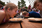 Alexandria Keyser of Priest River chows down on a fresh apple pie during Sunday's pie-eating contest at the City Park Bandshell as a part of the Fourth of July festivities. Keyser put up a good fight, but eventually lost the sixty second speed eating competition to Kaleb Hester, center right, of Athol...