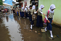 School girls using stepping stones along a flooded street, Tallo, Makassar, Sulawesi, Indonesia.