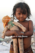 A young girl clutches a found doll at The Stung Meanchey Landfill in Phnom Penh, Cambodia.  She is one of the youngest workers at the dump, collecting bottles and cans to help her family on a daily basis.