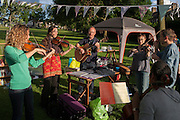 Members of the campaign to save nearby Carnegie Library in Herne Hill and closed by Lambeth council, organise a pop-up library and party in Ruskin Park, SE24 on 21st June 2016, in south London, United Kingdom. Local players improvise folk tunes in summer sunshine after their library was shut since 31st March. Children, the elderly and other adult groups have been prevented from using the building uphill from this location as Lambeth decide how to use the public space, bequeathed to the community by philanthropist, Andrew carnegie in 1911. (Photo by Richard Baker / In Pictures via Getty Images)