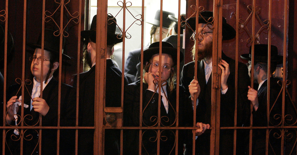 A group of ultra-Orthodox boys and men watch as the body of Grand Rabbi Moses Teitelbaum, worldwide spiritual leader of tens of thousands of members of the ultra-Orthodox Jewish sect, Satmar Hassidim, is carried into the Yetev Lev D'Satmar synagogue in Brooklyn, New York after he died in New York City at the age of 91 Monday 24 April 2006.