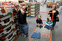 Chris Kotzian (L) reaches for some apples on a shopping trip with wife Barb (R) son Adam (2nd R) and daughter Avery (2nd L) in Thornton, Colorado March 25, 2010.  Chris, Barb and Adam are achondroplasia dwarfs with a rare genetic disorder of bone growth. Avery is average size. Preferring to be called little persons Chris and Barb are active in the Little People of America, the only dwarfism support organization that includes all 200+ forms of dwarfism.  REUTERS/Rick Wilking (UNITED STATES)