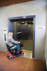 Woman driving electric mobility scooter entering a lift at a railway station,