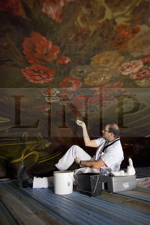 """© Licensed to London News Pictures. 04/03/2013. London, UK. On top of a scaffolding tower at around 40 feet in the air, restoration expert Francesco Rosellini works on the ceiling of the 'Painted Hall' at Greenwich Old Naval College in London today (04/03/2013). The conservation work, paid for by the Heritage Lottery Fund (HLF), is the 10th time the Painted Hall (often described as """"finest dining hall in Europe"""") will have been restored since its completion in 1784 and will have taken around five months to complete when the hall is unveiled to the public in May of this year. Photo credit: Matt Cetti-Roberts/LNP"""