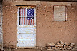 American Flag hanging in a door window of an adobe home in New Mexico