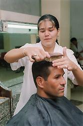 Female hairdresser brushing client's hair in hairdressing salon in Havana; Cuba,