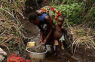 Karuba, Congo--Eurgenie Yarameni washes her clothes in a river stream during a moment of calm in this village. A rebel advance across Eastern Congo has displaced more than 250,000 people.  (Photo by Miguel Juárez Lugo)
