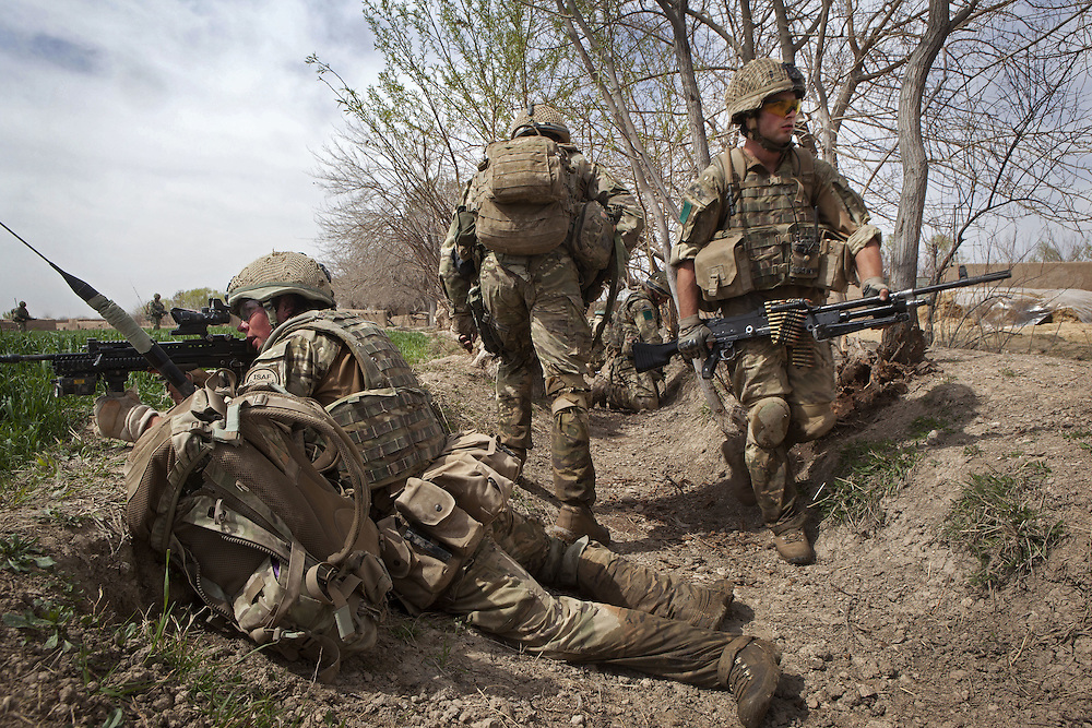 British soldiers of 3PARA use irrigation ditches and waterways for cover as they take up defensive positions during a foot patrol in Nad Ali, Hemand Province, Afghanistan on the 11th of March 2011.