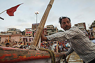 Boatmen pushing the boat Dashashwamedh Gath by the Ganges River in Varanasi, India.