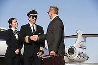 Mid-adult airline pilot and senior businessman shaking hands.