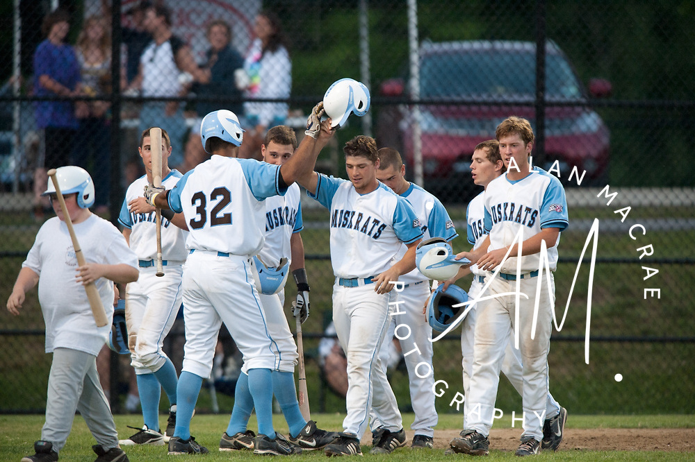 Muskrats' Casey Kalenkosky collects a round of high fives at home plate after a grand slam blast in Sunday's game against the Keene Swampbats at Robbie Mills Memorial Sports Complex.  (Alan MacRae/for the Citizen)