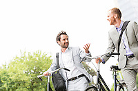 Businessmen talking while walking with bicycles outdoors
