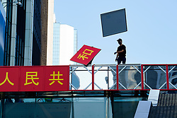Hong Kong. 1 October 2019. Protestor vandalises pro-China signs celebrating 70th anniversary of Peoples Republic of China during the march of 100,000 people from Causeway Bay to Admiralty.  Iain Masterton/Alamy Live News.