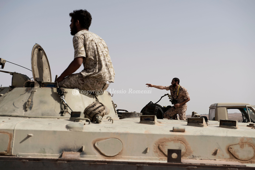 Libya: a fighter affiliated with Libya's Government of National Accord's (GNA) gestures from an apc (armoured personnel carrier) as he have seen a suspect movement on the frontline with ISIS. Alessio Romenzi