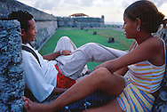 Dos jóvenes hablan sin desenfado, sentados sobre los altos muros de la muralla. Contemplando el paisaje, disfrutan del atardecer.  Cartagena de Indias,  2001 (Ramón Lepage / Orinoquiaphoto)     The fortified wall of Cartagena is in excellent condition and stretches more-or-less unbroken round a good portion of the Old Town. It is a pleasure for locals well as visitors to walk and observe the colonial architecture and excellent view of the Caribbean ocean..