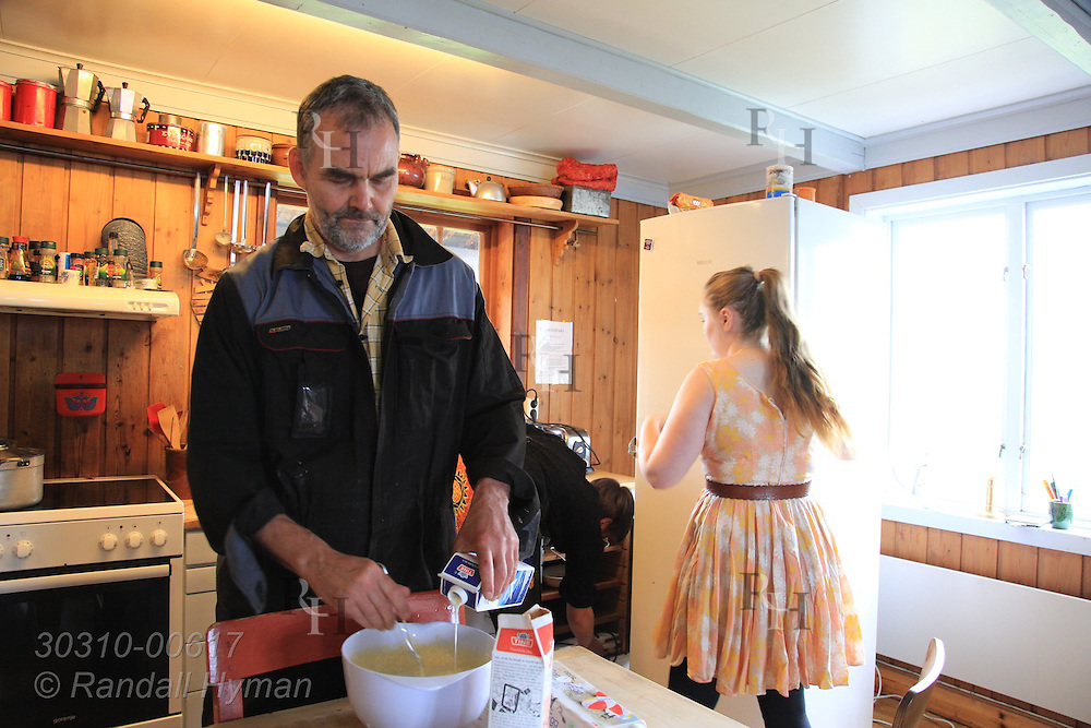 Georg Blichfeldt and his daughter make waffles in kitchen of Krakeslottet, an arts, concert and festival center on shores of Bergsfjord along National Tourist Route; Senja Island, Norway.