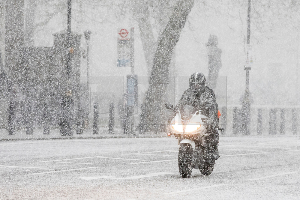 © Licensed to London News Pictures. 27/02/2018. London, UK. A motorbike battles through heavy snow on Whitehall in central London. Severe cold, blizzards and heavy snow are expected for the rest of the week as the 'Beast from the East' brings freezing Siberian air to the UK. Photo credit: Rob Pinney/LNP