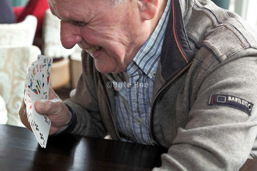 happy senior man playing cards