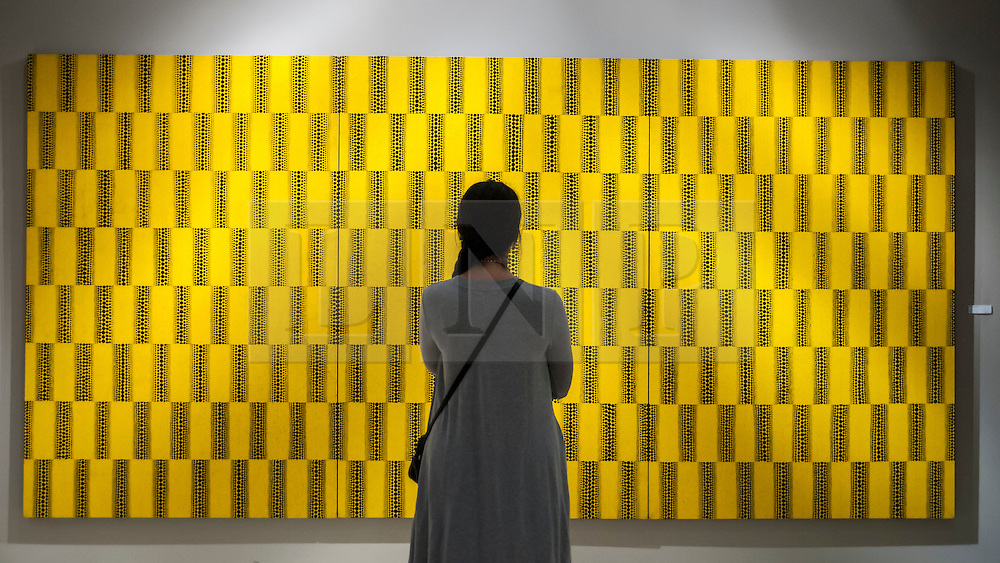 """© Licensed to London News Pictures. 24/06/2015. London, UK.   A visitor looks at Yayoi Kusama's """"Waves"""", at the preview of Masterpiece London, the international cross-collecting Fair for art, antiques and design which takes place at The Royal Hospital Chelsea 25 June to 1 July. Photo credit : Stephen Chung/LNP"""