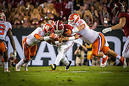 Clemson defenders #6 Dorian O'Daniel and #56 Scott Pagano tackle Alabama quarterback #2 Jalen Hurts.