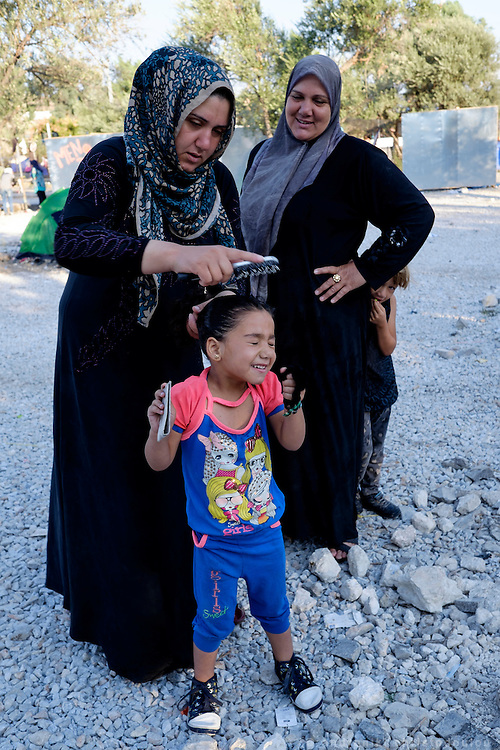 Mother combing her little girl's hair.<br /> Refugee camp Kara Tepe near Mytilene city. It hosts Syrian refugees who are waiting for their registration papers that will allow them to stay in Greece for some time till they can move to an other European country.